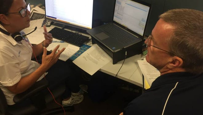Volunteers Liz Alward and Keith Gee are among the specialists answering calls for 2-1-1 Brevard, which has received more than 4,000 calls since Tuesday.