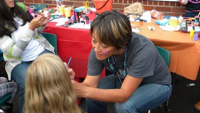 Stayton Elementary teacher Mika Hippen tends to the face painting at the Stayton Elementary School Fall Carnival.