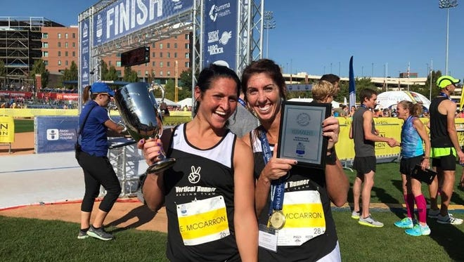 Emma and Grace McCarron show off their hardware after finishing first and third in the Akron Marathon over the weekend.