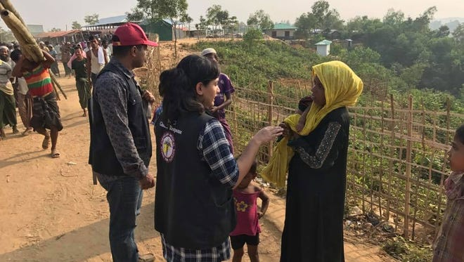 A doctor with the nonprofit Syrian American Medical Society speaks with a woman, holding her baby, at a camp for Rohingya refugees in Bangladesh on Tuesday.
