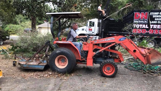 Darrell Bailey, owner of 87 Garage, operates a tractor on Saturday, Nov. 18, 2017, during a volunteer cleanup project in Navarre.