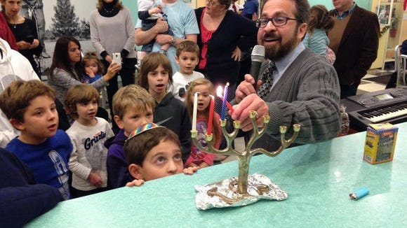 Cantor Scott Borsky lights the menorah at the Pop Shop in Collingswood.