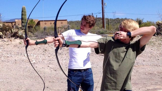 Weapons of all sorts seem to capture the interest of boys. Here Sawyer and buddy Landon try archery.