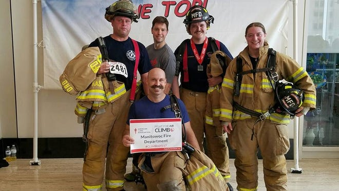 Pictured from left: Brian Kassube, Adam Theel, Phil Stodola, Ashley Engeldinger and Jacob Johnsrud (front) pose for a photo at the top of the U.S. Bank Center in Milwaukee after the 2017 Fight For Air Climb.