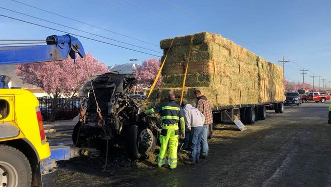 Crews clean up a hay truck fire in Gardnerville on Monday.