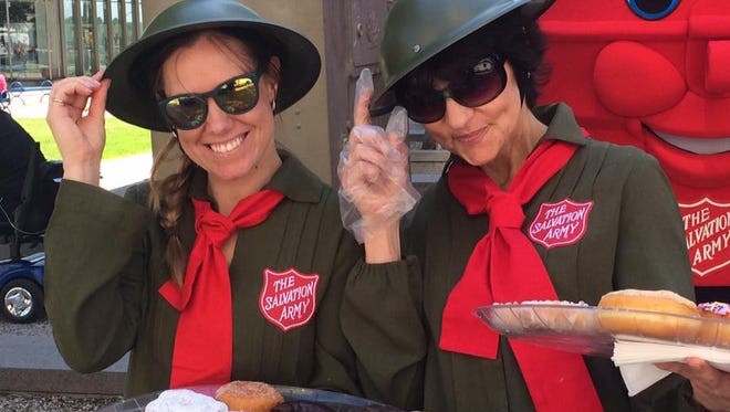 """Maureen Saponari (right) and Jenny Falls (left), handing out donuts in downtown Toledo on last year's National Doughnut Day, a holiday created to honor the """"Doughnut Lassies"""" who provided soldiers with the fried treat during World War I.  This Friday, volunteers from The Salvation Army will be giving away donuts at JT's Catawba Cafe and two Friendship stores."""