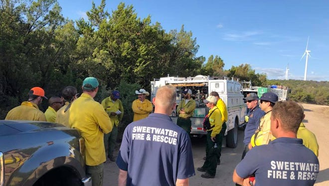 Crews involved in fighting Nine Mile Hill south of Sweetwater gather for a briefing Monday. The Texas Forest Service later Monday called the wildfire that consumed almost  1,000 acres contained.