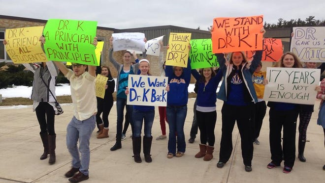 About two dozen Gibraltar High School students held up signs in support of former secondary principal Kirk Knutson before class Tuesday morning, with the School Board planning a closed-door meeting about the situation tonight.