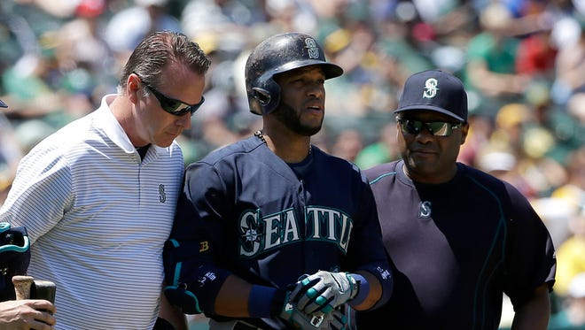 Seattle Mariners' Robinson Cano, center, walks to first base with assistant trainer Rob Nodine, left, and manager Lloyd McClendon  after being hit by a pitch during the sixth inning of a baseball game against the Oakland Athletics in Oakland, Calif., Sunday, July 5, 2015. (AP Photo/Jeff Chiu)