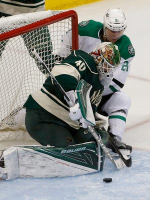 Minnesota Wild goalie Devan Dubnyk (40) swats away a shot by Dallas Stars left wing Antoine Roussel (21) during the third period of Game 3 in the first round of the NHL Stanley Cup playoffs in St. Paul, Minn., Monday, April 18, 2016. The Wild won 5-3. (AP Photo/Ann Heisenfelt)