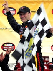 Travis Kvapil acknowledges the fans as he celebrates after winning the Michigan 200 truck race June 16, 2007, in Brooklyn, Mich. He won nine races in the series and the 2003 championship.