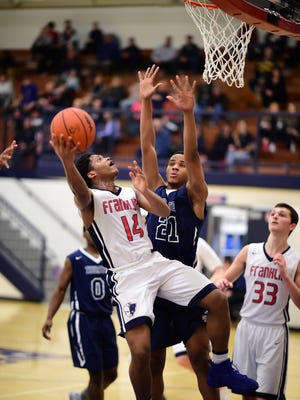 Livonia Franklin's Keyon Brown (14) looks to score over the defense of Redford Thurston's DeQuan Gadson (21). At right for the Patriots is Matthew Elrod (33).