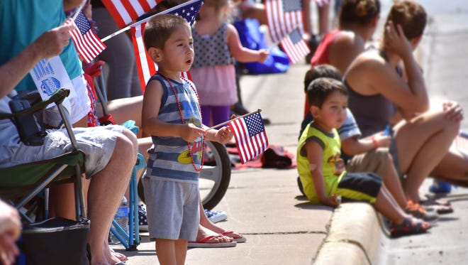 Aiden Buehler, 2, waves an American flag and watches intently as Alamogordo's Fourth of July parade passes by.