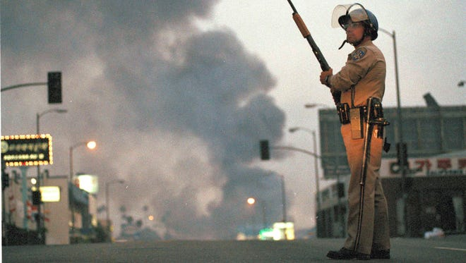 A California Highway Patrol officer stands guard in Los Angeles as smoke rises from a fire down the street April 30, 1992, the second day of unrest after the acquittal of four Los Angeles police officers in the Rodney King beating case.