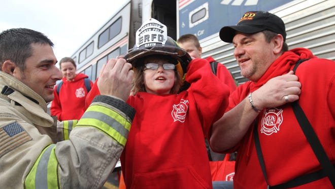 Gavin Steel, 5, of East Rochester and his family returned from a trip where they took a fantasy trip to the North Pole as guests of Operation North Pole, a volunteer charity.  He was greeted by East Rochester Fire Chief Mike Romach and given a hat with his name on it.  Joining him is Gavin Steel's father, Jason, who is also an East Rochester firefighter.