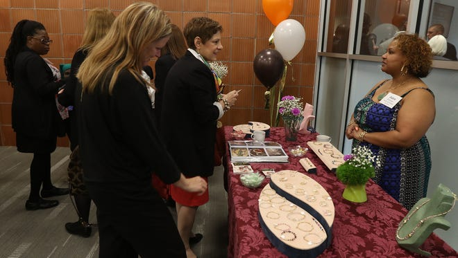 Jaira Santiago of Beads and Bangles displays her jewelry and chats with Francine Patella Ryan, public affairs manager with ESL Federal Credit Union.  Looking at the jewelry is also Sarah Clark, deputy state director with U.S. Senator Kirsten GillibrandÕs office.  Santiago was a member of the capacity builders cohort in the winter of 2014.