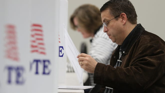 Joe Kunick votes on the school budget in Victor at Victor Intermediate School.