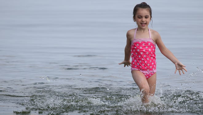 Iyana Santos, 4, of Greece splashes in Lake Ontario under the watchful eye of her grandmother, Jean Tartaglia, at Ontario Beach in Rochester. June 20 was the first day of summer.