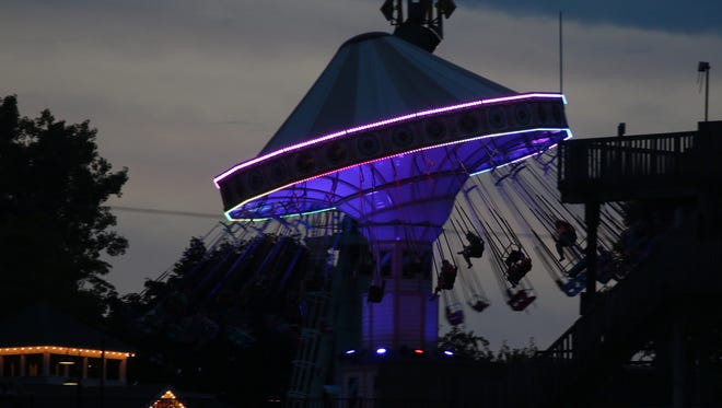 Patrons at Seabreeze Amusement Park are silhouetted against a sunset sky in Irondequoit.