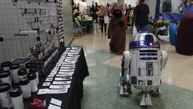 Nicky Blum of Greece, portraying Jawa with R2D2, walks through a vendor area.   Blum is with 501st Legion, a non profit group that makes appearances in movie accurate costumes from the Star Wars movies.  The group also raises money for charities.