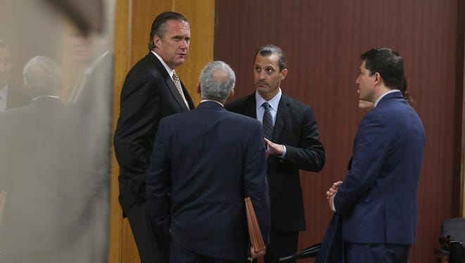 The defense attorneys in the Rideout trial huddle near the elevators to speak before court started.  Michael Schiano talks to Matthew Parrinello, David Pilato, Julie Cianca (just behind Pilato) and Michael DiPrima (back to the camera).