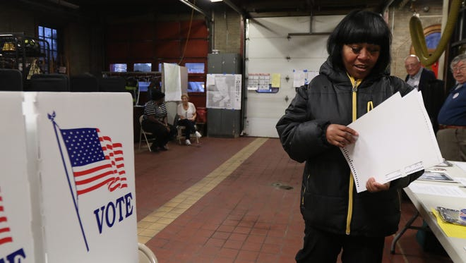 Kelicia David heads to a privacy area to cast her vote at the Genesee Street fire house.  Polls opened at 6 a.m.