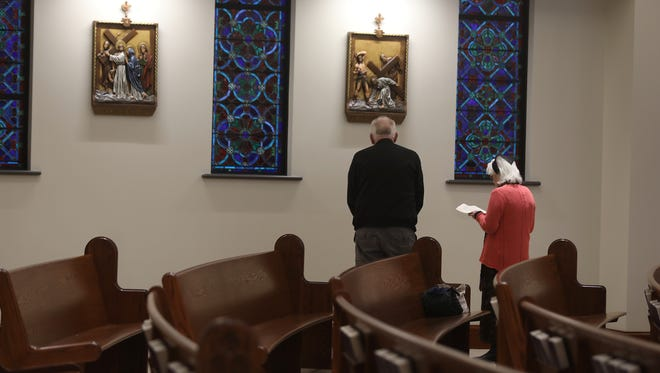 Jim Burke and Gerry Resch pray at the Stations of the Cross.  The Stations of the Cross were donated by St. Vincent dePaul Church in Corning.