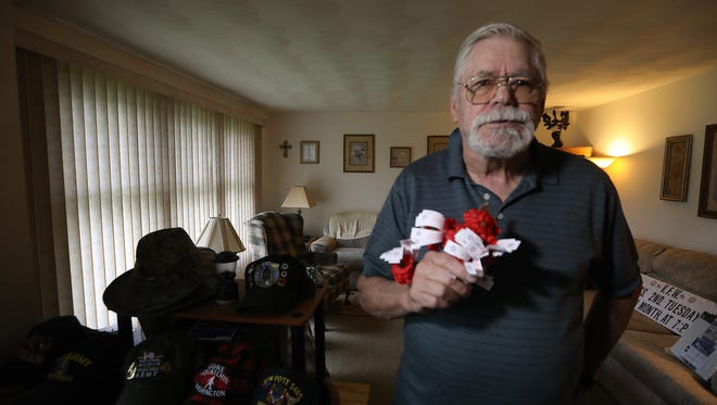 Joe Jakus, a life member of the Rice-Hallick VFW Post No. 5465 in Henrietta, holds a fistful of poppies that the United States Postal Service will no longer allow veterans like him to distribute to passersby on post office property.