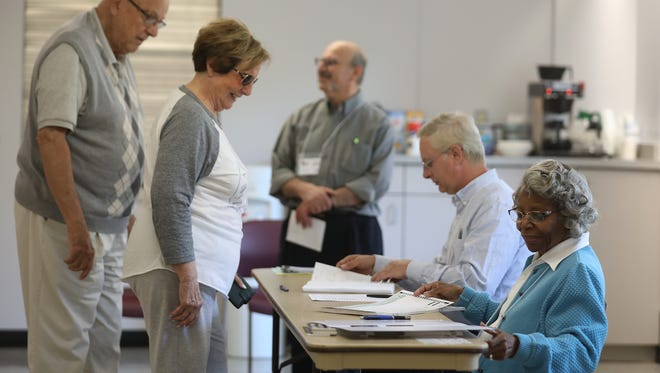Arnold Ciaccio and Nancy Sciarebba, domestic partners, check in wth Thelma Haizlip, an election inspector to vote at Brighton Fire Department Station 1 Headquarters.    Joining Haizlip are other election inspectors, seated beside her is Dana McClure and standing is Ethan Alderman.