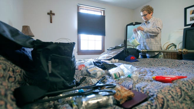 Lucille Frisicano, a retired nurse from Webster, packs Tuesday for her trip to Liberia, where she will help people with Ebola. She's going with Heart to Heart International and will be there for at least six weeks.