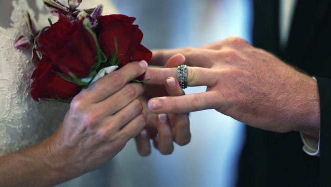 Luanne Round slips a ring on the finger of her husband Matthew Round on Feb. 14, 2013 in West Palm Beach, Fla.