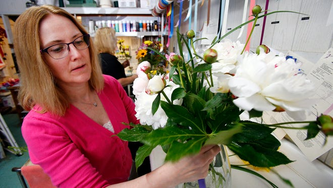 Stacey Cofka works on a display of fresh-cut peonies at her Berkeley store, A Blossom Shop on Route 9.