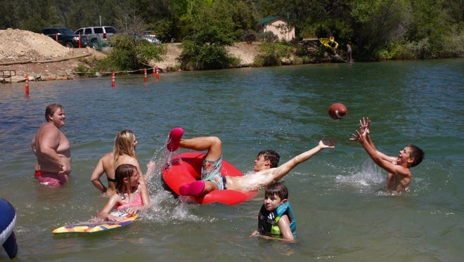 Jeremy Lack, left, watches as Matthew Braden dives for a football at Oak Bottom amphitheater on Sunday in Whiskeytown National Recreational Area.