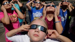 People practice using eclipse glasses in Kansas City,