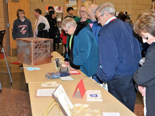 Attendees examine some of the student-made museum artifacts