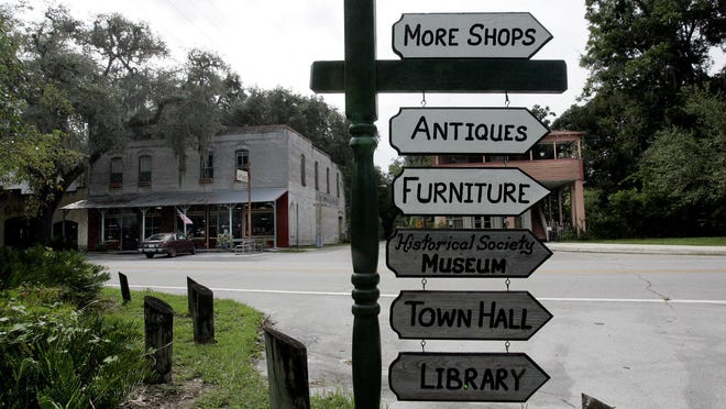 A wooden sign in downtown Micanopy directs visitors to antique shops, a museum, library and furniture. Micanopy has a population of about 630 and is known as a shopping and antiquing mecca.