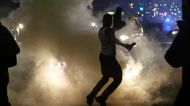 Protesters run when police shoot tear gas in Ferguson, Mo., on Sunday. Protests over the killing of 18-year-old Michael Brown by a police officer have entered their second week.