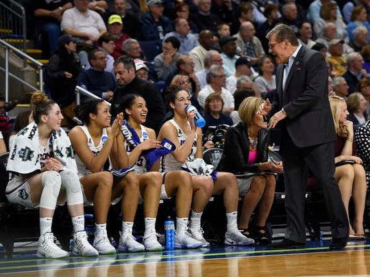 Connecticut head coach Geno Auriemma, right, jokes with Katie Lou Samuelson, left, Napheesa Collier, second from left, and Gabby Williams, center, and Kia Nurse as the clock winds down on their 90-52 win over Oregon in a regional final game in the NCAA women's college basketball tournament, Monday, March 27, 2017, in Bridgeport, Conn.