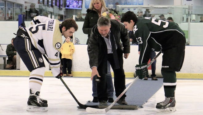 Indian Hills' Justin Ferrari (left) and Ramapo's Michael Pear during ceremonial puck drop. Dave Altana is dropping the puck with his wife, Jill, looking on.