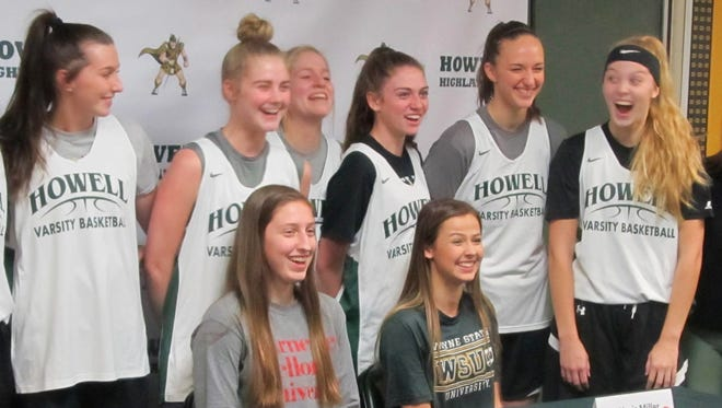 Howell's Leah Weslock (front row, left) and Alexis Miller (front row, right) laugh with basketball teammates while posing for a photo during their college signing ceremony Thursday.