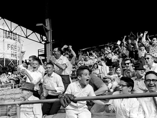 Fans along the first base line leap to their feet and roar in approval as a drive by Billy Joe Davidson sails over the right field screen in the 9th inning of the first game of two, giving the Nashville Vols an 8-6 victory over Mobile at Sulphur Dell April 23, 1961.