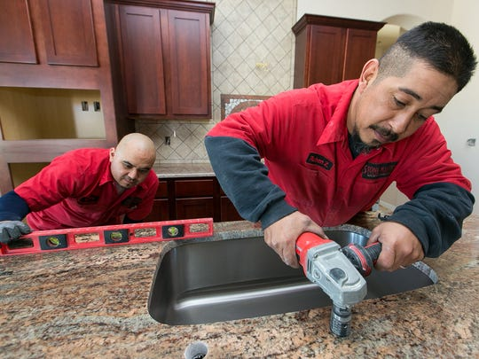 Stone Masters head granite installer Ruben Zamora, right, and Manny Casillas, installer,  work Thursday in the kitchen of a home located on Little Creek Court.