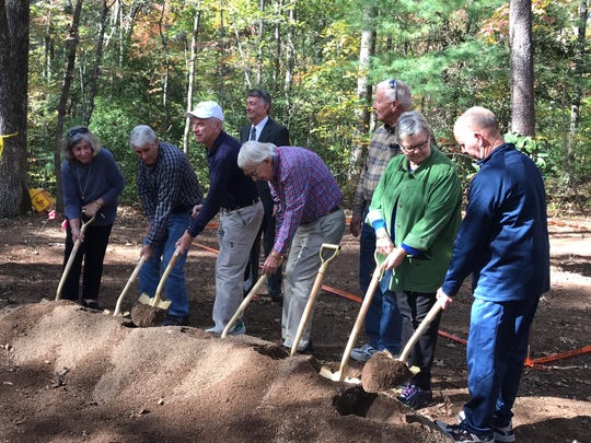 Descendants and relatives of Samuel Burdine, including Nancy Patton Simmons, on the left end, break ground at the site where their ancestor's cabin will be moved, at Hagood Mill Historical Site near Pickens.