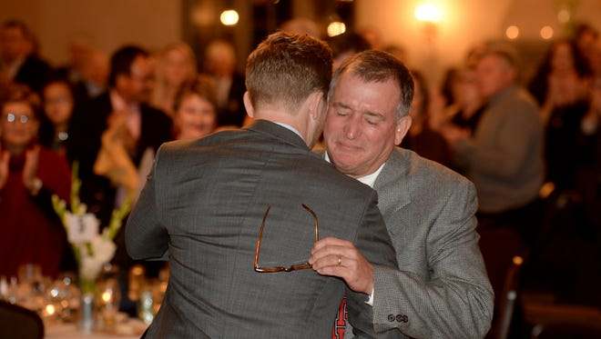 Carl Runnels hugs Skip Runnels, right, after introducing his father Thursday, Nov. 19, 2015, for his induction into the Indiana Golf Hall of Fame at Forest Hills Country Club in Richmond.
