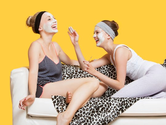 Stock image. Two young women applying face mask while