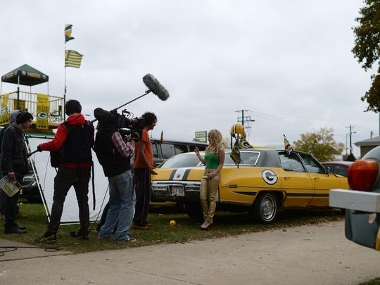 "Nick Greco (in orange) plays the part of Polano in a scene where he asks Dana Daurey's character Vanessa for money to park  as a crew films ""The 60 Yard Line"" at the house on the corner of Oneida Street and Stadium Drive Green Bay on Friday."