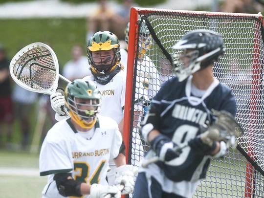 Burr and Burton goalie Natty Eisenman, center, watches the action behind his net during the Division II boys lacrosse championship game on Thursday at Castleton State College.