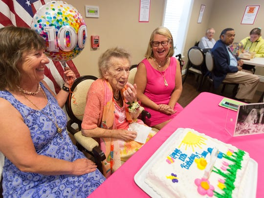 Flanked by her daughters Charlene Gilbert, left, and Kathryn Gilbert, Jean Gilbert sneaks a taste of icing from her birthday cake during her 00th birthday celebration at Services for Older Citizens in Grosse Pointe Farms on Tuesday, June 5, 2018.