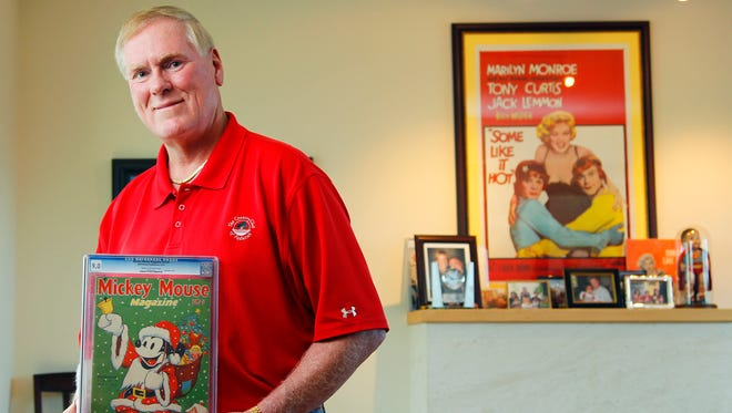 In this photo taken on May 19, 2014, John C. Wise, poses in his San Diego home with a 1937 Mickey Mouse Magazine.  Though the magazine is not for sale, he is auctioning off some rare historic comic books from his collection. (AP Photo/U-T San Diego, K.C. Alfred)  NO SALES, NO ARCHIVING, TV OUT, MAGS OUT,   TABLOIDS OUT.