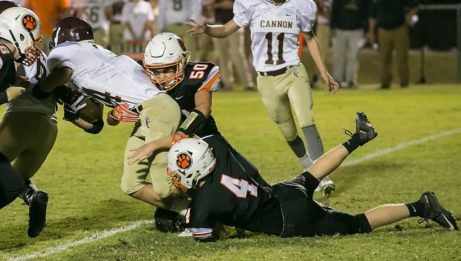 Middle Tennessee Christian's Mason McDonald (50) and Spencer Simmons (4) wrap up Cannon County's Jaydon Coon during Friday's game.